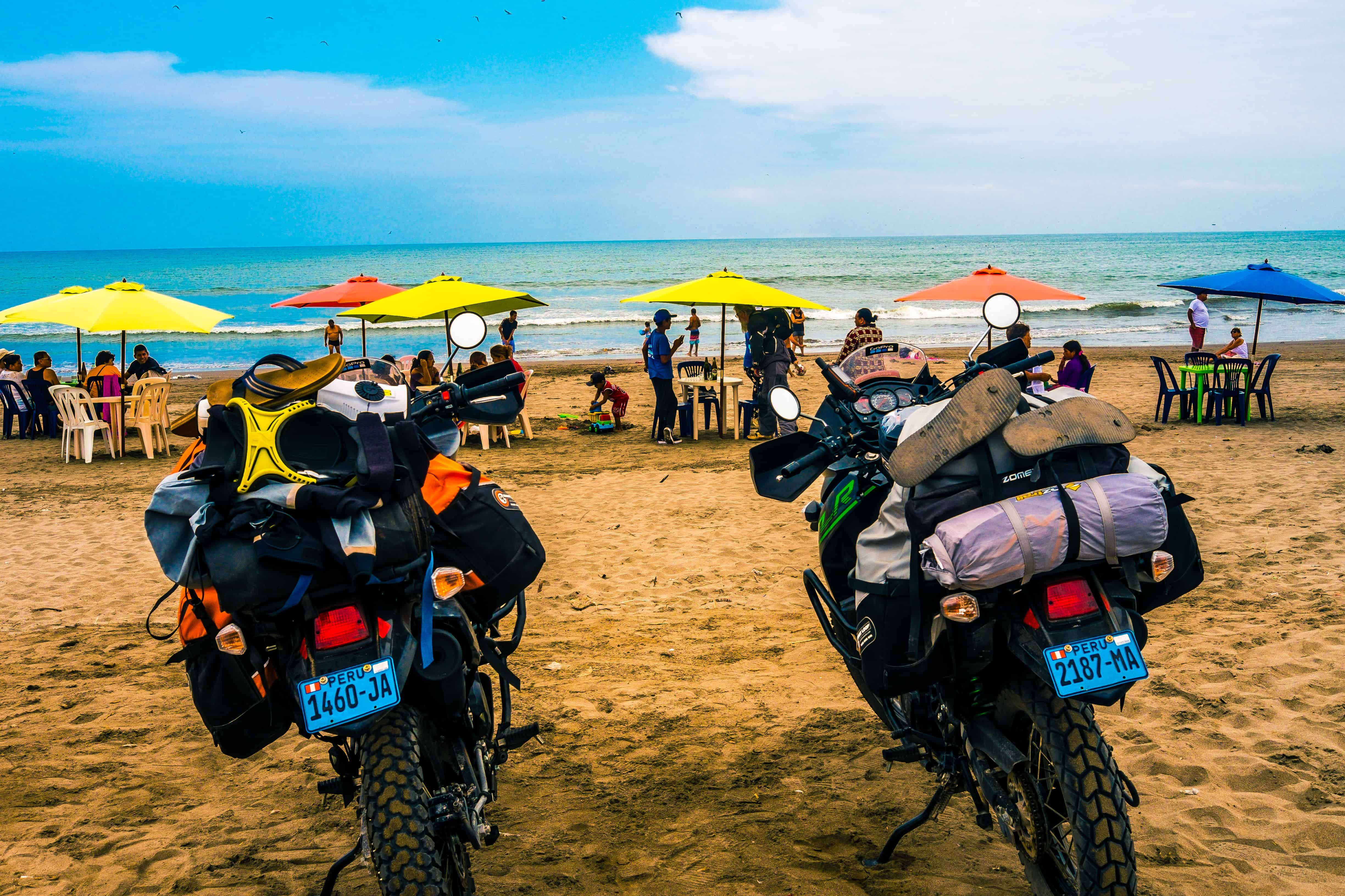 two KLR650's parked at a beach in Peru with Giant Loop great Basin Saddlebags