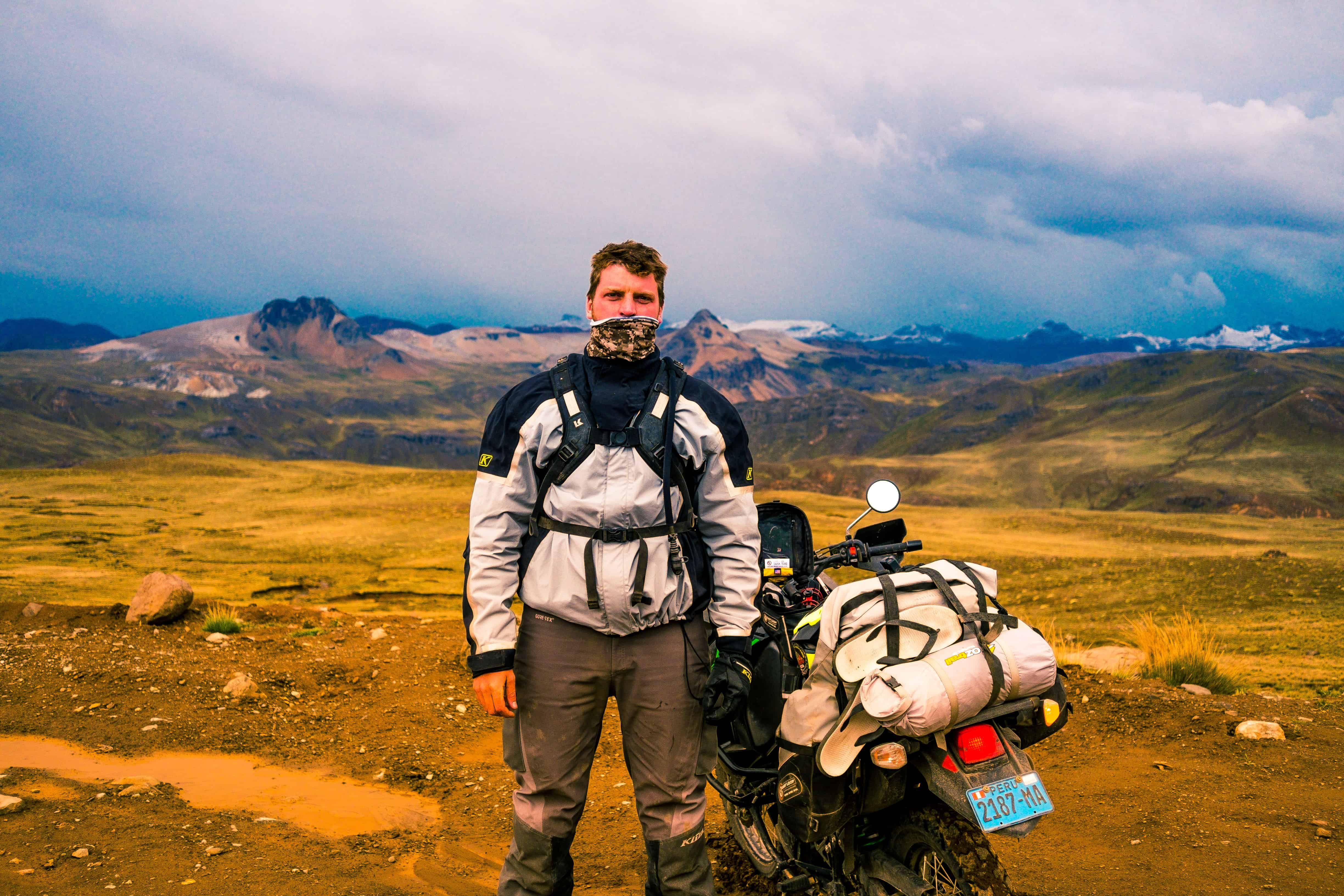 Toby Richardson standing in front of a snow capped mountain with his motorcycle in the Andes, Peru.