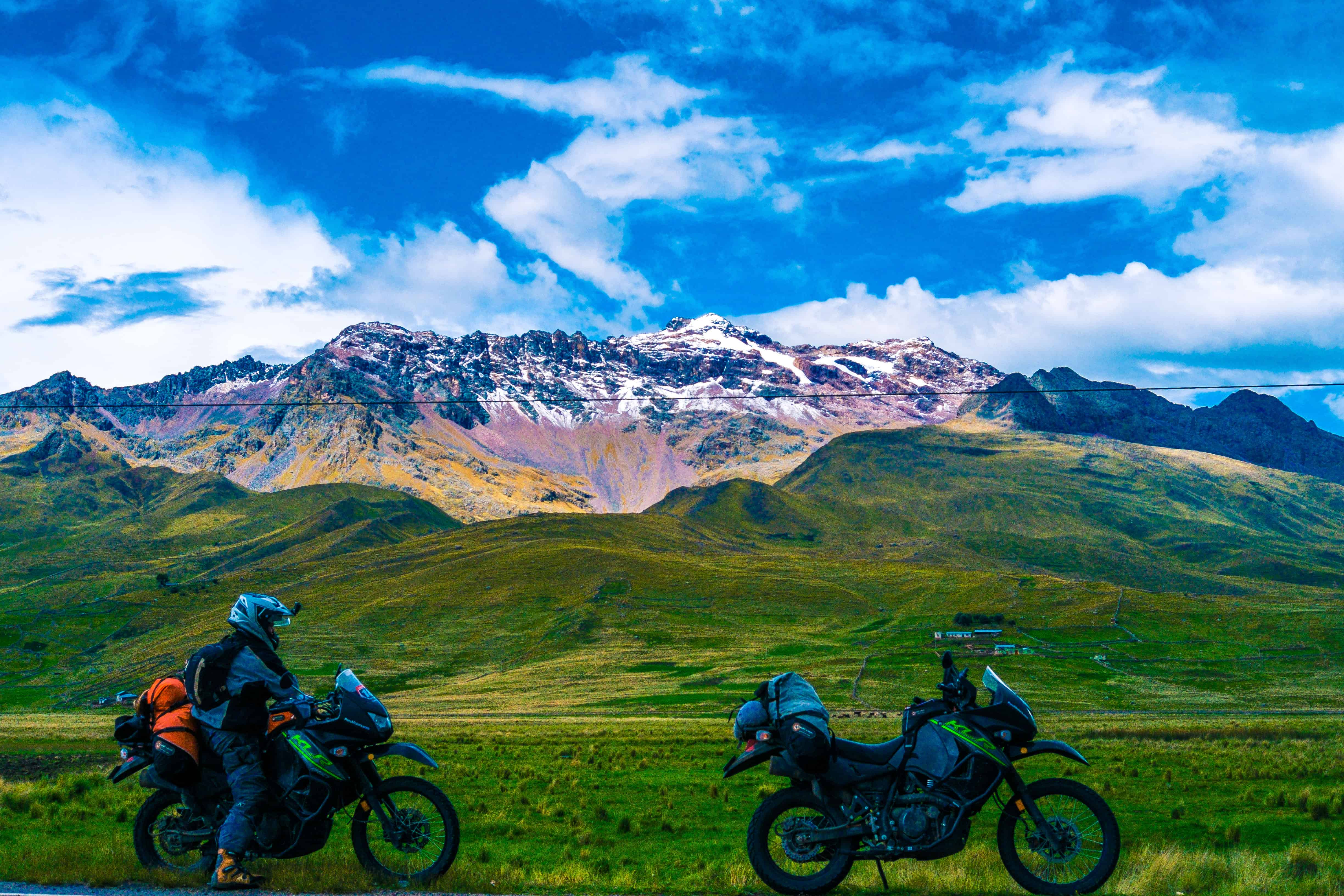 Two KLR650 motorcycles in front of a snow capped mountain in the Andes, Peru